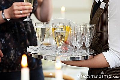 Waiter serving champagne and orange juice