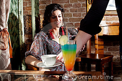 Waiter serving woman with coffee and beverage