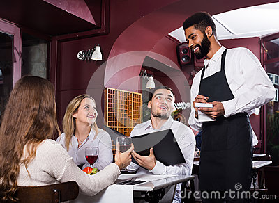 Waiter taking care of adults at cafe table