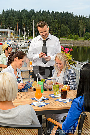 Waiter taking orders sidewalk bar from women