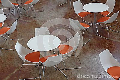 Waiting room with tables and orange and white chairs