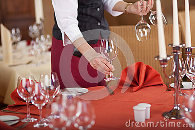 Waitress Arranging Wineglasses On Restaurant Table