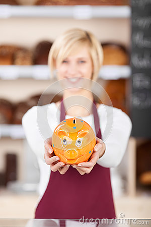 Waitress Holding Piggybank At Bakery Counter