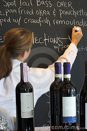 Waitress, menu board, and wine