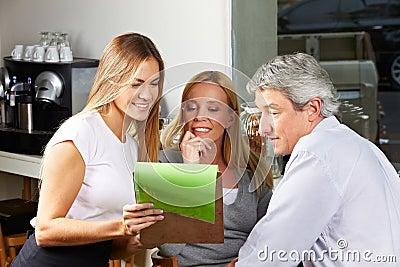 Waitress offering menu to seniors
