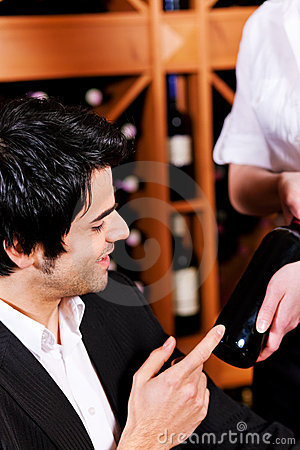 Waitress offers a bottle of red wine