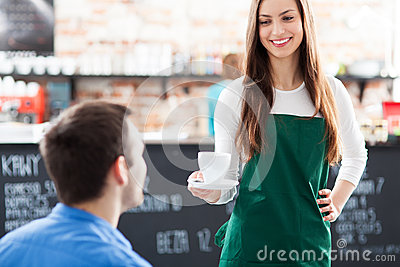 Waitress serving man coffee