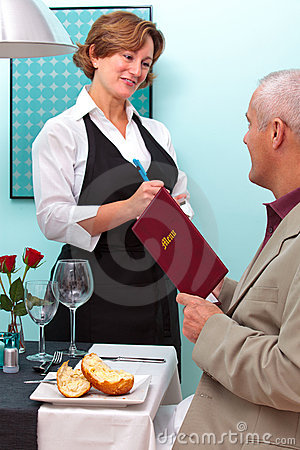 Waitress taking a food order from a man.