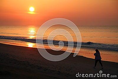 Walker on the beach at sunrise