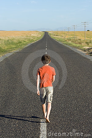 A Boy Walking Away From A Girl Little boy, aged eight, wearing a red shirt, waling down a tarred road ...