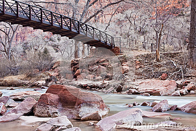 Walking bridge over calm river with red rocks