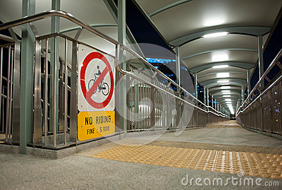Walkway across a bridge with a no riding sign