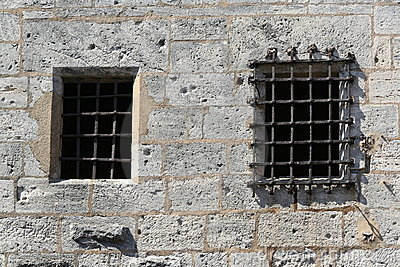 Wall of a castle with barred window