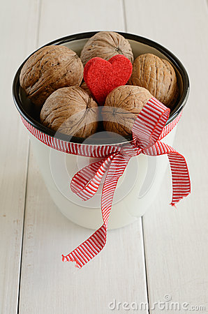 Walnuts in white cup bounded up in red ribbon