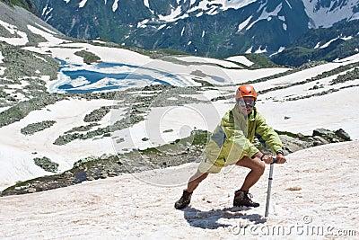 Wandelaar met ijs-bijl op sneeuw.