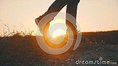 Wanderer, der draußen bei Sonnenuntergang auf dem Felsen geht Beine in den Trekkingsstiefeln gehen entlang den Gebirgsrücken gege