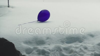 A wandering purple balloons floats on the snow stock footage