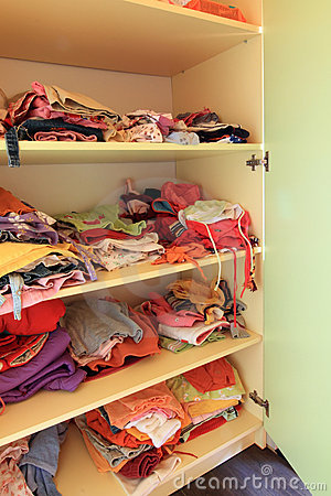 Wardrobe with child clothes on shelves