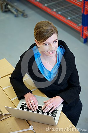 Warehouse employee typing on laptop computer