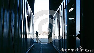 Warehouse worker opening metal door. Blue steel tone. Full HD