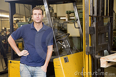 Warehouse worker standing by forklift