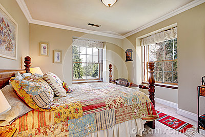 warm colors bedroom with an old fashioned bed stock image