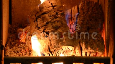 Warm cozy fire in a home fireplace. Real wood burning in a brick fireplace. Home coziness. Indoor open fireplace burning and heating up living room close up stock video footage