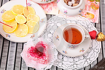 Warm cup of tea, heart shaped cake and sweets
