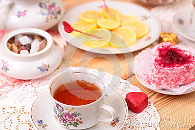 Warm cup of tea, lemon and sweets