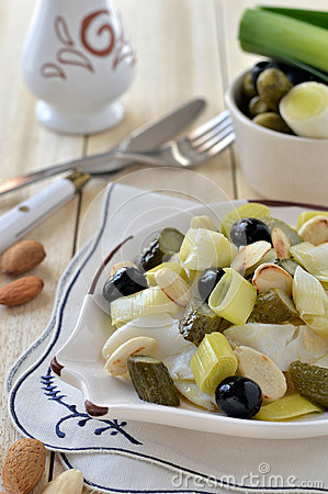 Warm Salad with dried cod, leek, almonds on a plate in the shape of a ...