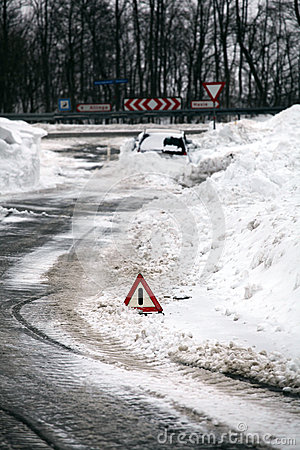 Warning triangle, car in snow pile.