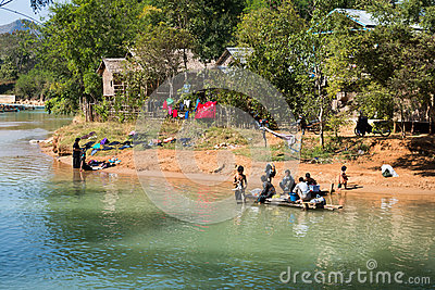 Washing and laundry in clean lake canal water Editorial Stock Image