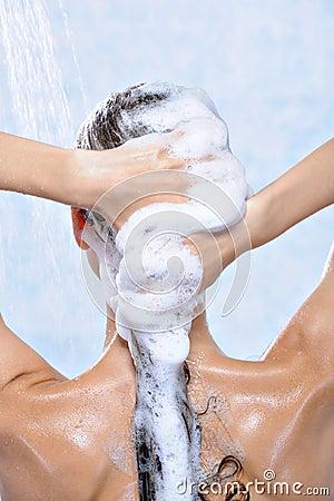 Washing long brunette female hair by shampoo