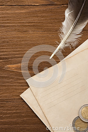 Watch and ink feather at envelope