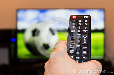 Watching soccer / football game on modern tv, with a close-up of Stock Photo