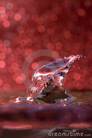 Water drop collision against a red background