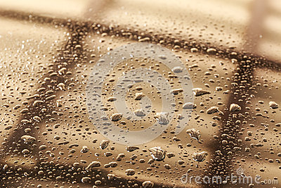 Water drops in a shiny metallic surface with table re