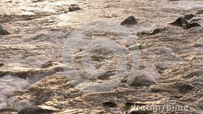 Water flowing over small rocks in river lit by afternoon sunset light stock footage