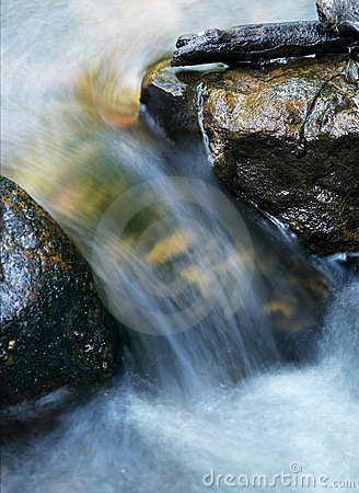 Water Flowing And Rushing Between Rocks