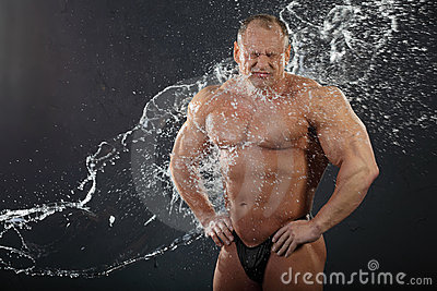 Water flows on undressed bodybuilder