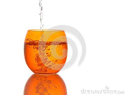 Water poured into beautiful orange colour glass - splashes. Isol