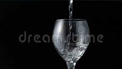 Water pouring into wine glass. In slow motion stock footage
