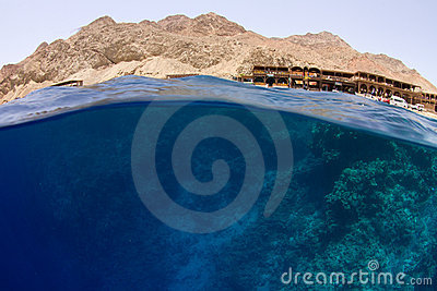 Water with reef and desert mountains