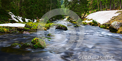 Water of river flows through mossy rocks Stock Photo