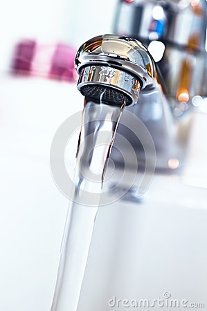 Water tap with flowing water in the bathroom