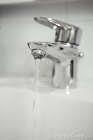Water tap with focus on water coming out of tap