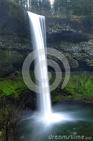 Waterfall cascading over mossy rocks with mist