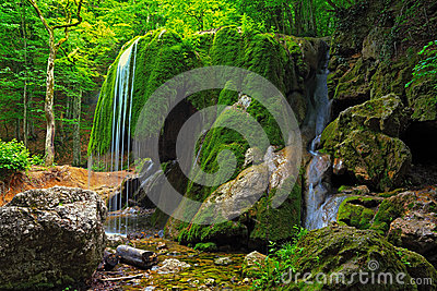 Waterfall in Crimea forest and wet mossy stone