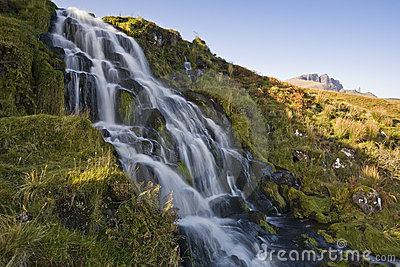 Waterfall flowing down hill with sky and mountains