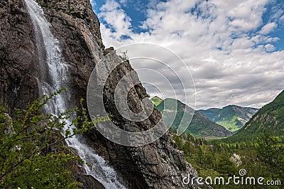 Waterfall rocks mountains sky